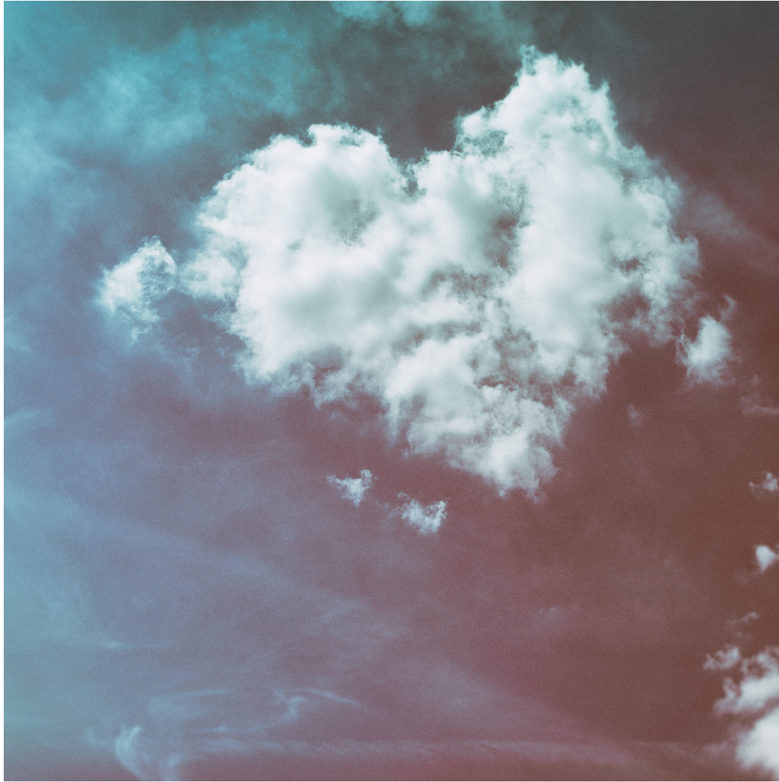 Photograph of a heart-shaped cloud in a blue sky